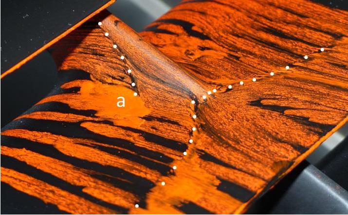 Zviditelnění povrchových proudnic v okolí poměrně masivní varianty tlumicí opěrky. Oblast odtržení, označená v Obrázku 1 písmenem (a), je zřetelně vidět.